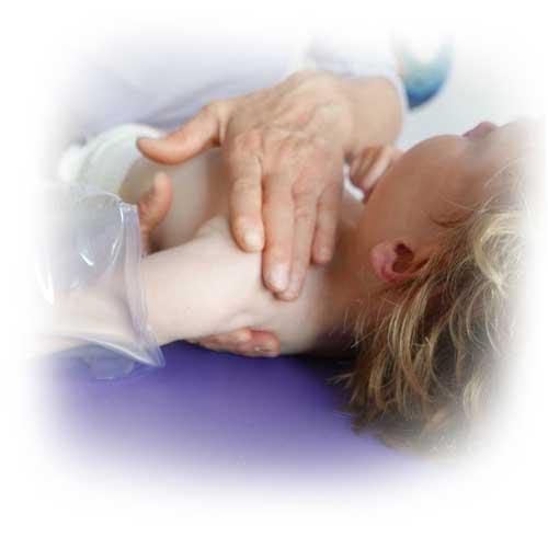 Fyzioterapeutka provádí manuální terapii na rameni dítěte.
