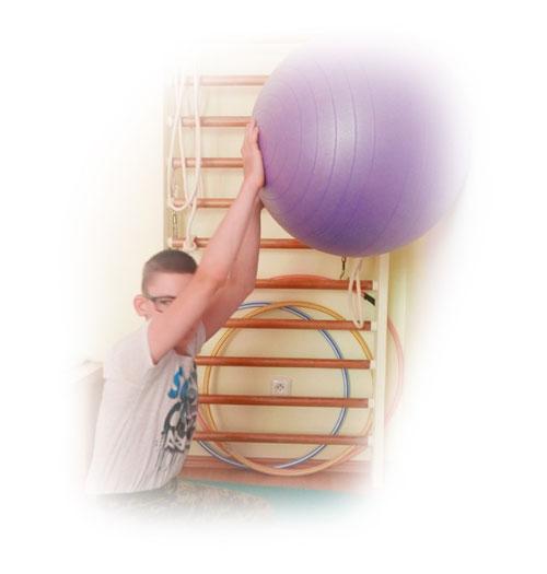 Chlapec během cvičení s míčem u stěny.